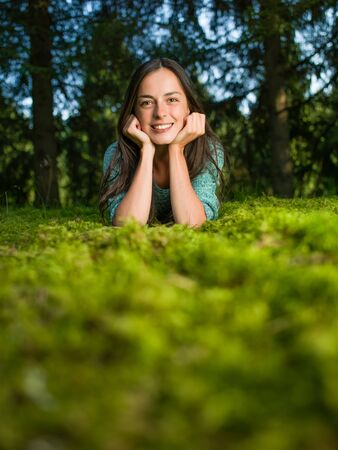 lies down: beautiful young woman lies down on the grass smiling with woods in the background Stock Photo