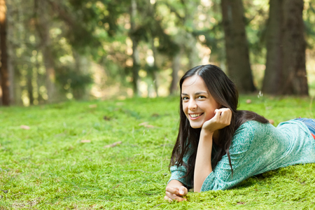 lies down: beautiful young woman lies down on the grass smiling