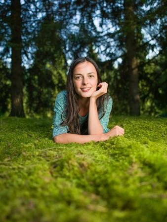 mujer sola: hermosa mujer joven se acuesta en la hierba sonriendo con maderas en el fondo Foto de archivo