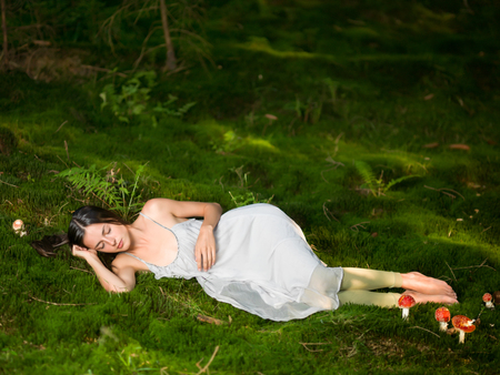 moos: Beautiful woman in the forest dressed as a fairy sits on green moss with the poisonous Amanita sleeping
