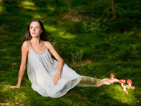 moos: Beautiful woman dressed as a fairy sits on green moss with the poisonous Amanita looking