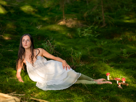 moos: Beautiful woman in the forest dressed as a fairy sits on green moss with the poisonous Amanita looking