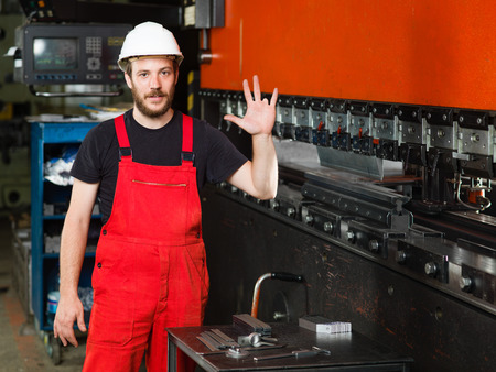 ring finger: front close-up of a worker, with his left hand raised, showing his left ring finger missing, wearing red overalls, and a white protective helmet, standing next to an industrial machinery, painted in red and black, with a control panel in the background, i
