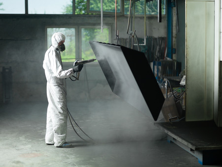view of a worker wearing a full white protective suit and breathing mask, sand blasting a metal crate hung from a metal beam in the ceiling of an industrial hall Reklamní fotografie - 54021688