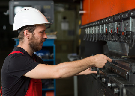 computerised: right side close-up of a worker, wearing red overalls, and a white protective helmet assisting an industrial machinery, painted in red and black, with a control panel in the background, in an industrial setting Stock Photo