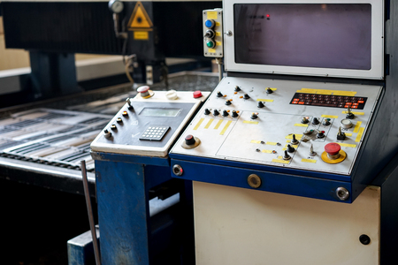 computerised: front close-up of the control panel of a laser cutting machinery, with knobs, switches and labels on it, and a screed