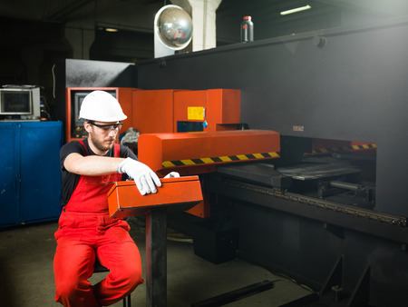 computerised: close-up of a man in red overalls, wearing white protective helmet and gloves, and protection glasses, sitting on a chair, operating a red-and-black-painted heavy-duty machinery, in an industrial hall Stock Photo