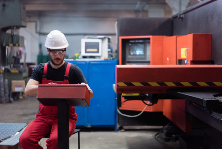 computerised: man in red overalls, with a white protective helmet and protection glasses, sitting on a chair, operating a red-painted heavy-duty machinery, in an industrial hall Stock Photo