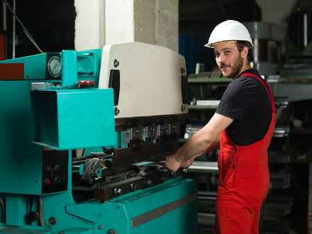 computerised: left side view of a worker, standing, wearing red overalls, and a white protective helmet holding a metal plate inside an industrial bending machine, painted in turquoise and white, with another machine in the background, in an industrial setting Stock Photo
