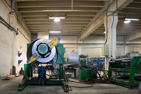 computerised: right side view of a heavy-duty green machine with a swivel holding a roll of metal sheet being unrolled into a flatting mill, with hoses and wires hanging out, in an industrial hall