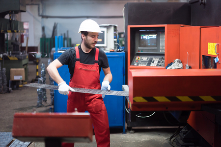 computerised: man in red overalls, wearing white protective helmet and gloves, standing, handling a sheet of metal plates onto the table of a red-painted heavy-duty machinery, in an industrial hall