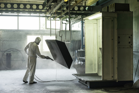 blasting: view of a worker wearing a full white protective suit and breathing mask, sand blasting a metal crate hung from a metal beam in the ceiling of an industrial hall