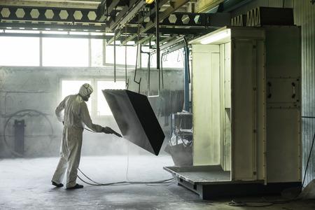 weergave van een werknemer het dragen van een volledig wit beschermend pak en ademhaling masker, zandstralen een metalen kist hing aan een metalen balk in het plafond van een industriële hal