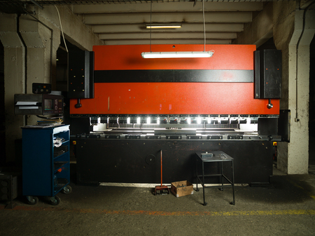 computerised: front view of an industrial machinery, painted in red and black, with a control panel and a table next to it, in an industrial setting Stock Photo