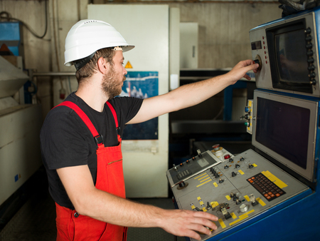 computerised: right side close-up of a man wearing red overalls and a white protective helmet, standing, operating the control panel of an industrial machinery, in an industrial hall Stock Photo