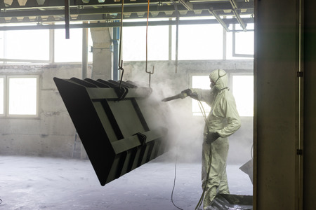 residue: view of a worker wearing a full white protective suit and breathing mask, sand blasting a metal crate hung from a metal beam in the ceiling of an industrial hall