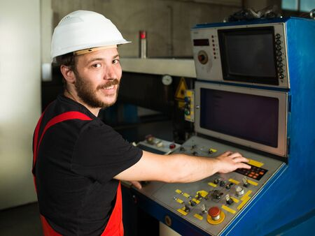 computerised: right side close-up of a worker looking happy, wearing red overalls and a white protective helmet, standing, operating the control panel of an industrial machinery, in an industrial setting Stock Photo