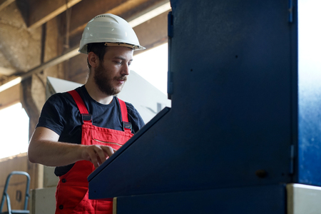 computerised: right side close-up of a worker looking busy, wearing red overalls and a white protective helmet, standing, operating the control panel of a blue painted industrial machinery, in an industrial setting Stock Photo