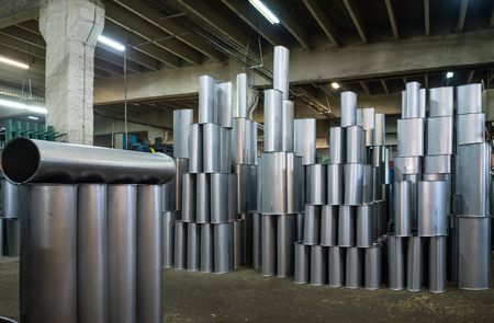 computerised: close-up of manufactured silver metallic tubes stacked together upright, on the floor of an industrial hall Stock Photo