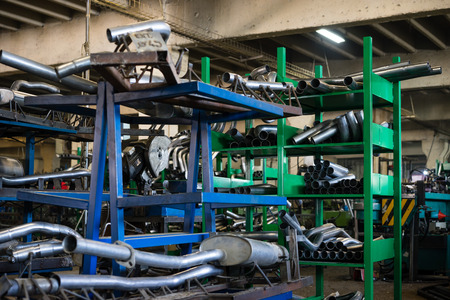 Welded: close-up of blue and green metal shelves containing oval tubes and round silver metal pipes, straight and bended, and assemblies comprised of these pieces welded together, in an industrial setting