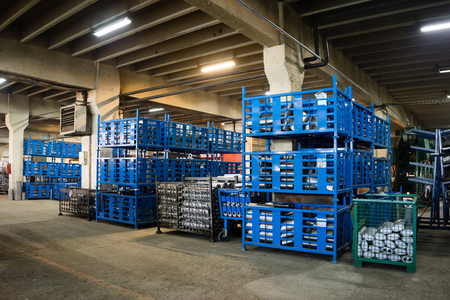 residue: view of an industrial hall, with big blue, green, and grey metallic bins, containing different elements which make up exhaust pipes and accessories