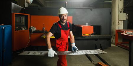 computerised: front view of a worker, looking happy, wearing red overalls, white protective helmet and gloves, standing, holding a sheet of metal plates in front of a red-painted heavy-duty machinery, in an industrial setting