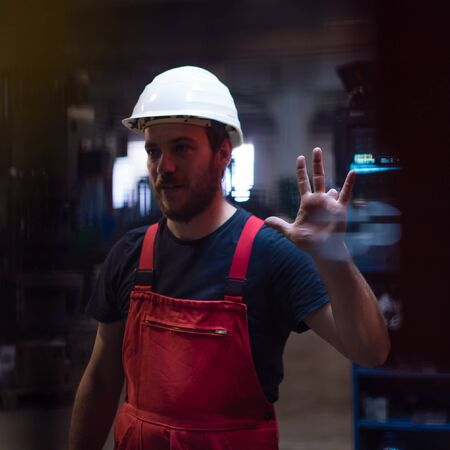 ring finger: dynamic close-up of a worker wearing red overalls and a white protective helmet, with his left hand raised, showing his left ring finger missing, in an industrial setting Stock Photo
