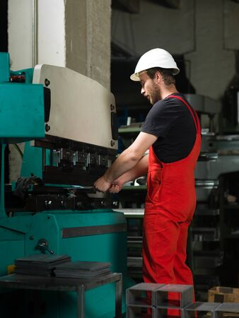 utensils: left side view of a worker, standing, wearing red overalls, and a white protective helmet operating an industrial machinery, painted in turquoise and white, with another machine in the background, in an industrial setting