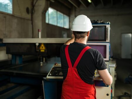 computerised: view from behind of a man wearing red overalls and a white protective helmet, standing, operating the control panel of an industrial machinery, with a laser head, in an industrial hall