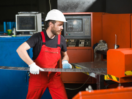 computerised: right side view of a worker wearing red overalls, white protective helmet and gloves, standing, handling a sheet of metal plates onto the table of a red-painted heavy-duty machinery, in an industrial setting Stock Photo