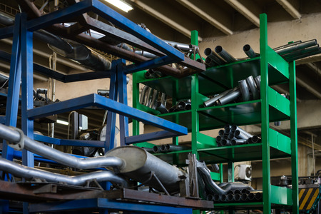 assemblies: close-up of blue and green metal shelves containing oval tubes and round silver metal pipes, straight and bended, and assemblies comprised of these pieces welded together, in an industrial setting