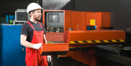computerised: front view of a worker looking in the distance, wearing red overalls, white protective helmet and gloves, standing next to the control panel of a red-and-black-painted heavy-duty machinery, in an industrial setting