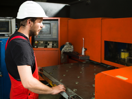 computerised: right side view of a worker in red overalls, wearing a white protective helmet, standing, looking at the table of a red-painted heavy-duty machinery, in an industrial setting