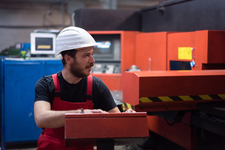 computerised: man in red overalls, with a white protective helmet, sitting on a chair, operating a red-painted heavy-duty machinery, in an industrial hall