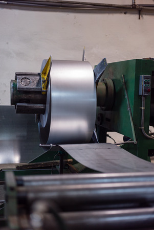 sheet metal: close-up of roll of metal sheet unfolding from a swivle which is attached to a heavy-duty green machine, in an industrial setting