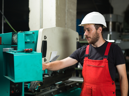 computerised: left side view of a worker, standing, wearing red overalls, and a white protective helmet, operating the control panel of an industrial bending machine, painted in turquoise and white, with another machine in the background, in an industrial setting