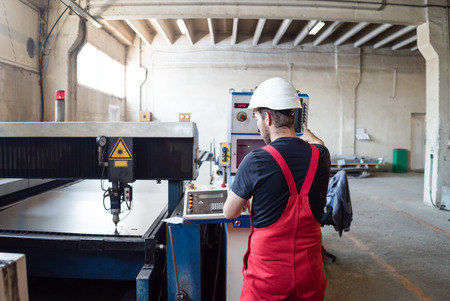 computerised: view from behind of a man wearing red overalls and a white construction helmet, standing, operating the control panel of a robotic arm with a laser head, in a big industrial hall