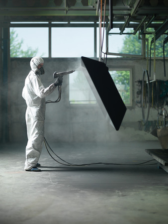 view of a worker wearing a full white protective suit and breathing mask, sand blasting a metal crate hung from a metal beam in the ceiling of an industrial hall