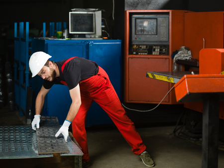 bending over: front view of a worker, wearing red overalls, white protective helmet and gloves, bending over and picking up a sheet of metal plates, in front of a red-painted heavy-duty machinery, in an industrial setting Stock Photo