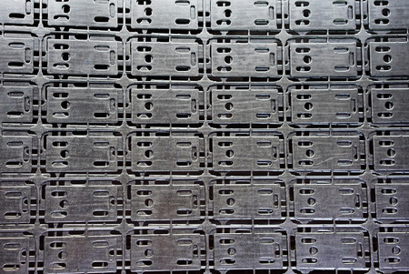 computerised: close-up of an array of stencilled plates, cut into a steel sheet