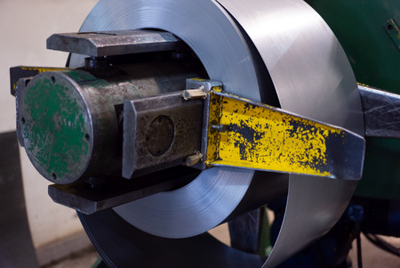 computerised: close-up of roll of metal sheet unfolding from a swivel, which is attached to a heavy-duty green machine, in an industrial hall
