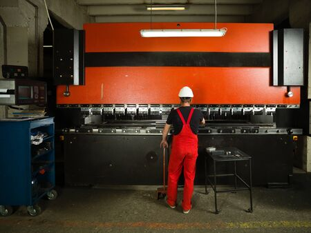 industrial machinery: back side view of a worker, standing, wearing red overalls, and a white protective helmet operating an industrial machinery, painted in red and black, with a control panel and a table next to it, in an industrial setting