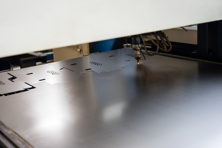 computerised: close-up of a laser head, cutting stenciled patterns into metal sheets
