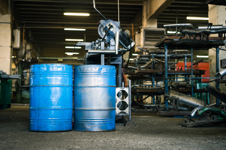 safety gear: view of two blue industrial barrels with the paint worn off,  laid upright on the floor of an industrial hall, with shelves full of metal pieces of exhaust pipes and metal manufacturing devices in the background