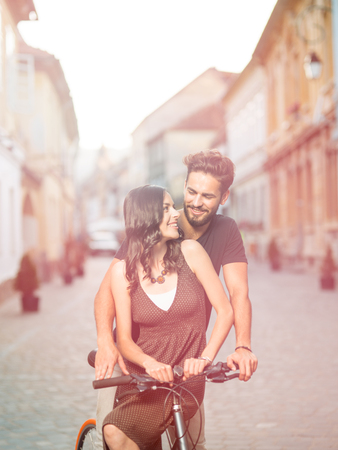 be dressed in: handsome young man with blue eyes stops cycling to be eye to eye with his beautiful partner dressed in brown dress with polka dots on a street in the old town centre Stock Photo