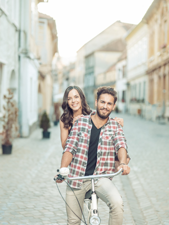Happy young couple going for a bike ride in the city on a sunny summer day