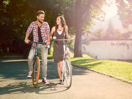 smiling couple on the bike in an alley with green trees on a sunny summer day