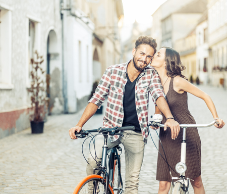 be kissed: handsome young man with blue eyes stops cycling to be kissed on the cheek by his beautiful partner dressed in brown dress with polka dots on a street in the old town centre