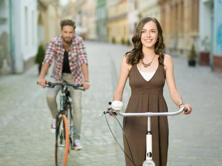 casual woman: handsome young man dressed casual  follows a beautiful young woman dressed in brown dress with white dots on bikes