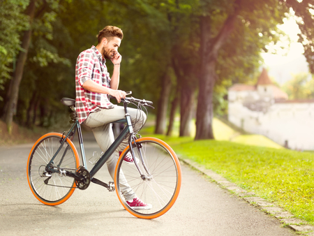 answer phone: Handsome young man stops cycling to answer  his smart phone sitting on a bike in an alley with green trees